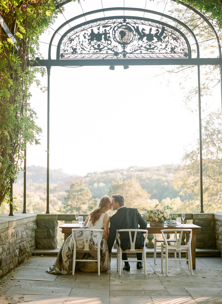 Bride and groom sitting down In white chairs under an iron arch kissing in front of a lush garden