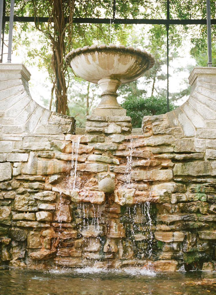 Tall fountain flowing over cement blocks under an arch with ivy flowing