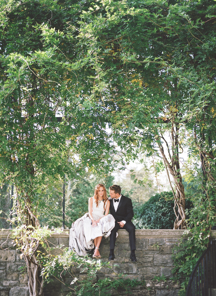 Couple sitting on a stone wall dangling their legs with lush green trees hanging over them