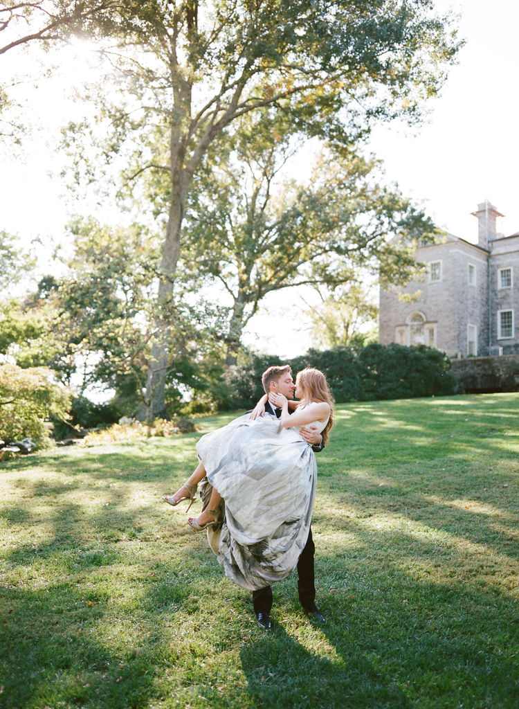 Groom carrying his bride in the grass kissing her with a large mansion in the background