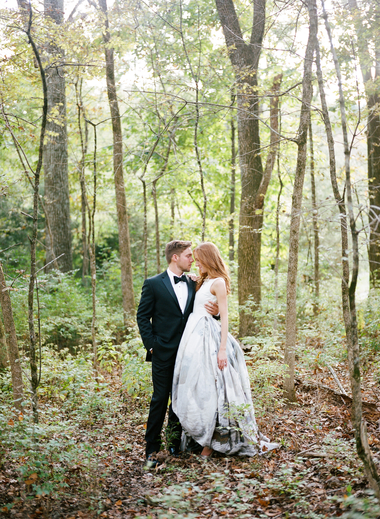 Bride and groom posing for a picture in the forest with trees all around them