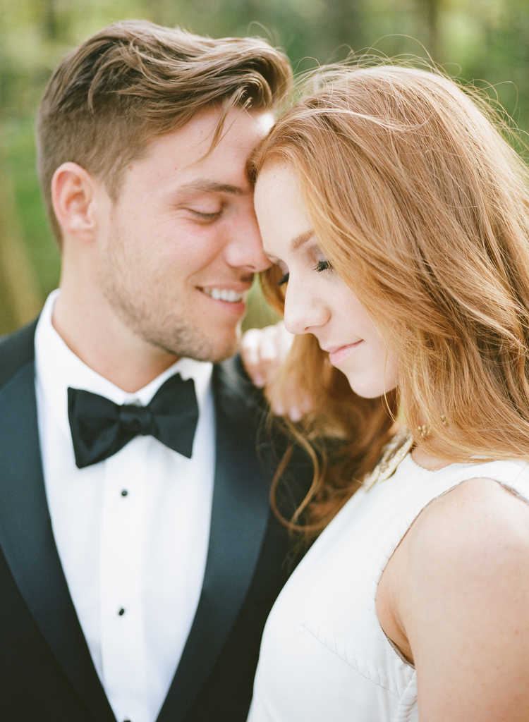 Up close photo of a groom in a black and white tux looking at his bride