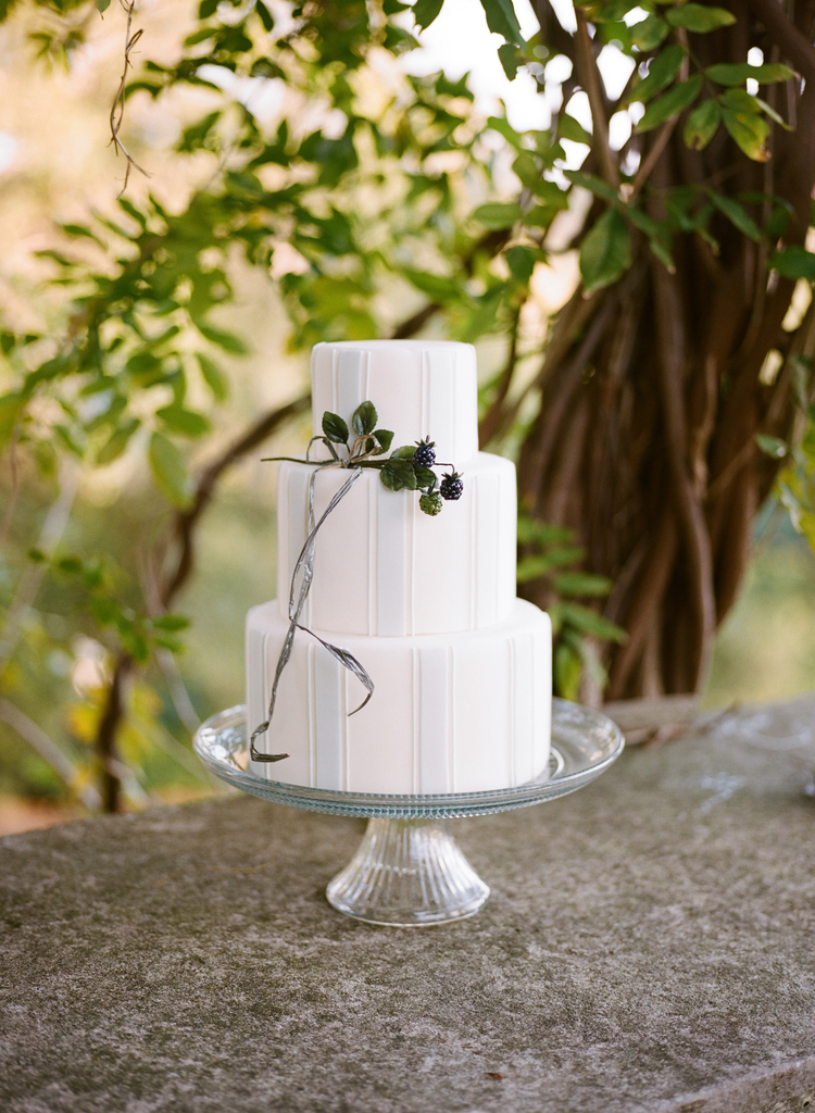 3 tier blue and white striped cake with a branch of blackberries hanging on the side