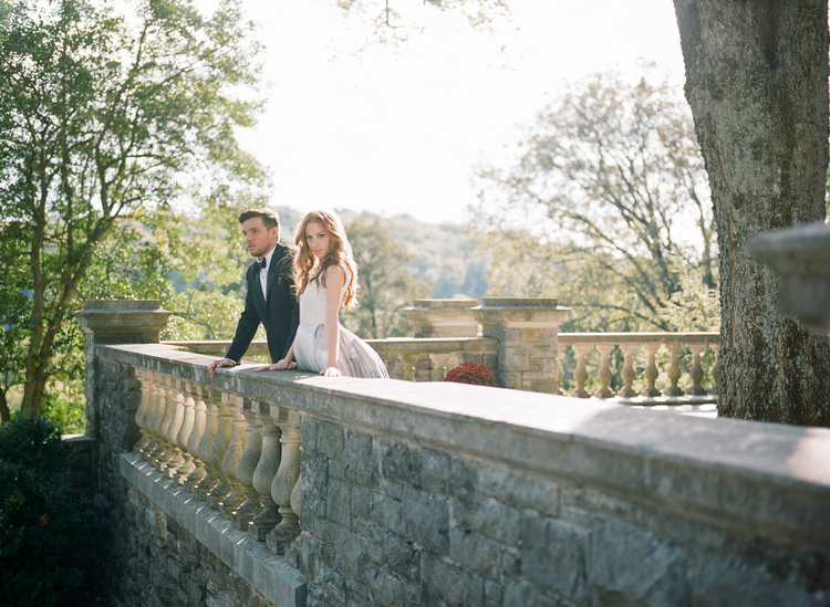 Bride and groom looking over a stone wall balcony with the light shining on them