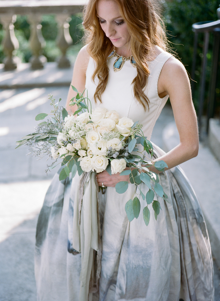 Bride holding an all white rose and eucalyptus bouquet while wearing a gold a turquoise necklace