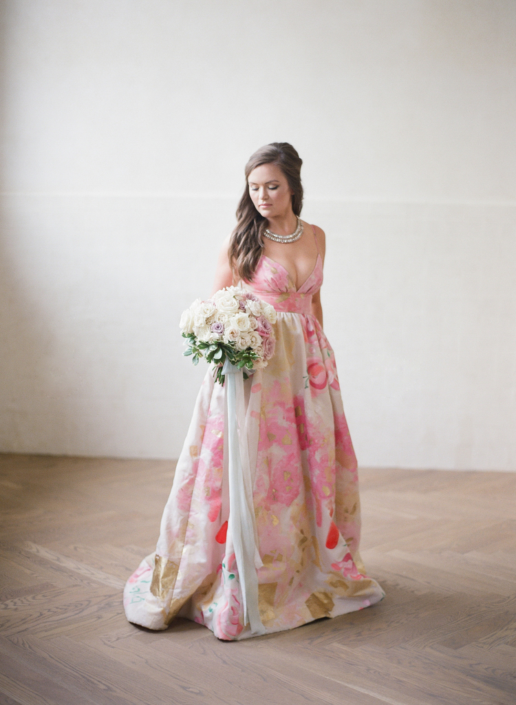 Bride holding her bridal bouquet wearing a pink and gold abstract floral dress