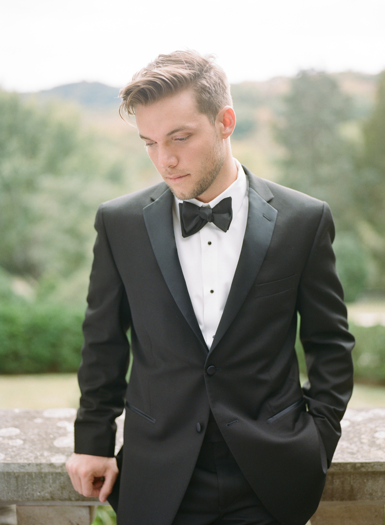 Groom in a black and white tux standing by a balcony