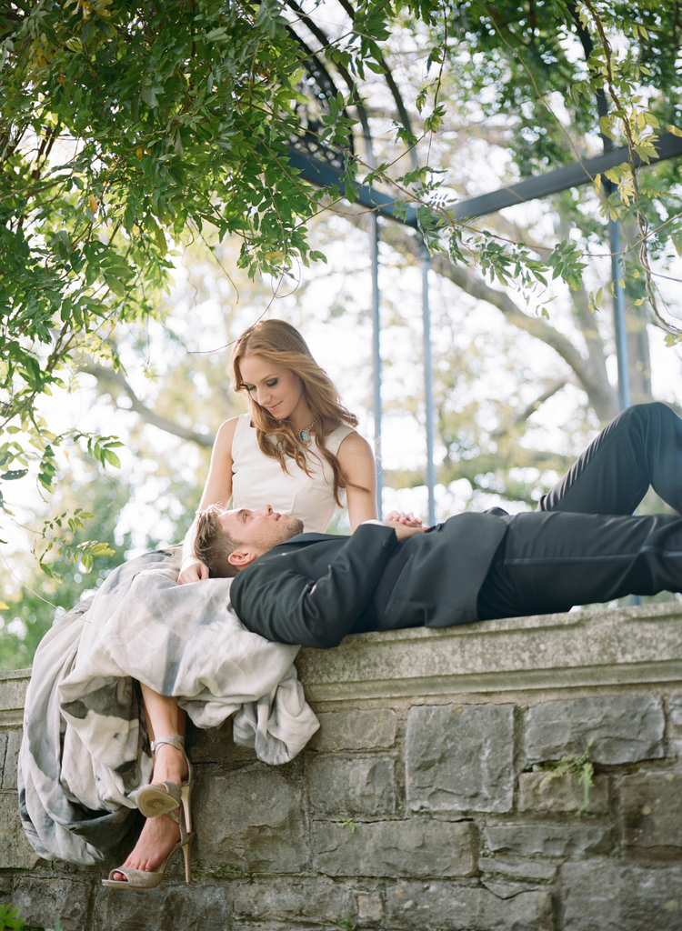 Bride sitting on a balcony with her groom laying over her lap looking up at her with a lush green tree above them