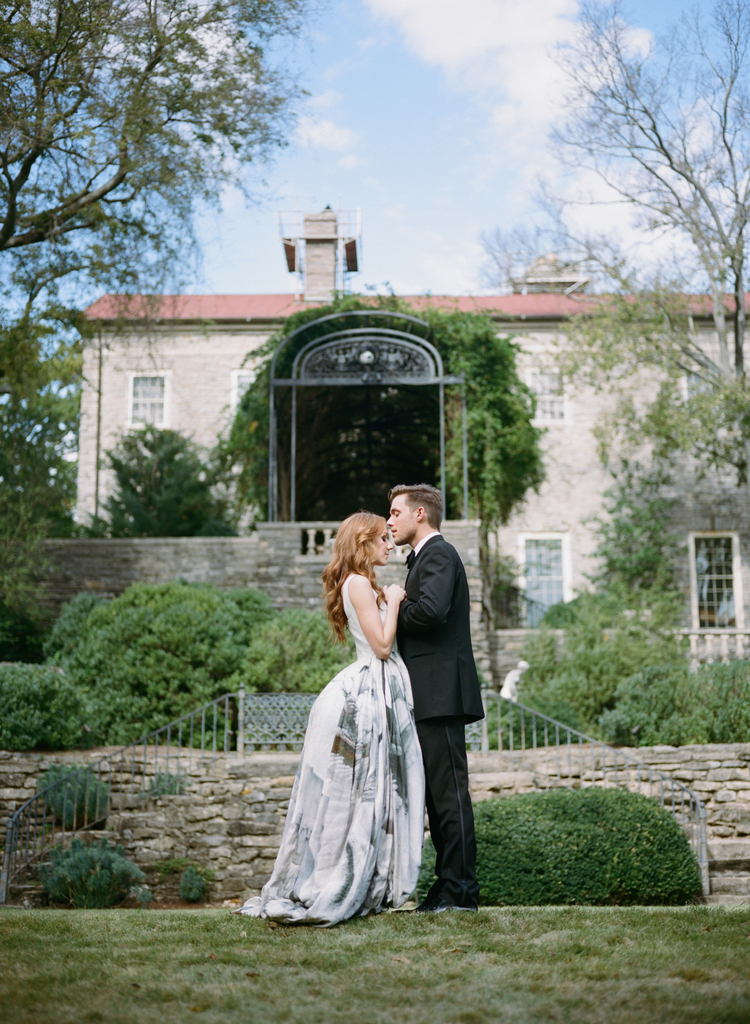 Couple standing in the grass in front of a beautiful house and the groom is going to kiss the brides forehead