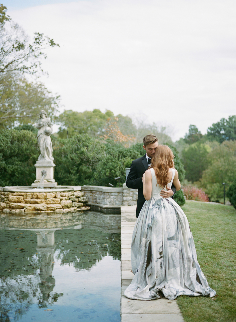 Bride and groom standing by a pool with a stone sculpture while they are talking to each other