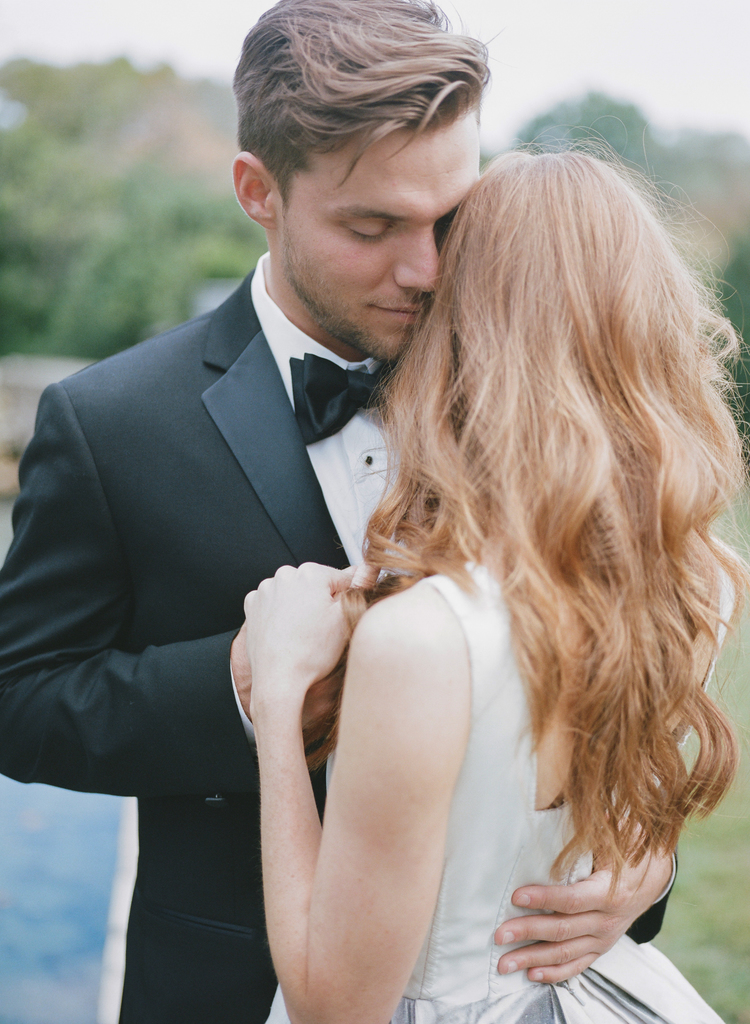 Bride and groom holding hangs whispering to each other lovingly