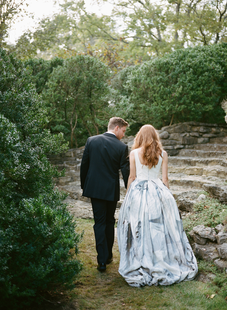 Couple walking up stone steps in their wedding attire