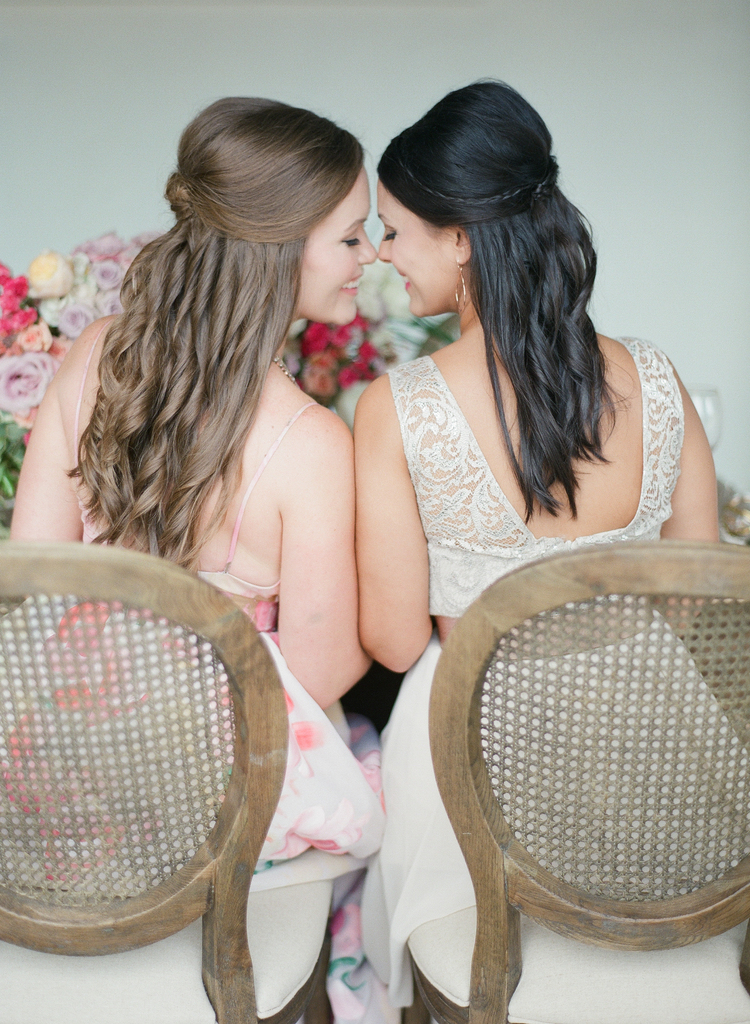 Brides touching heads sitting in two chairs smiling at each other