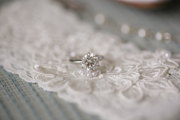 Classic solitaire silver engagement ring sitting on white lace