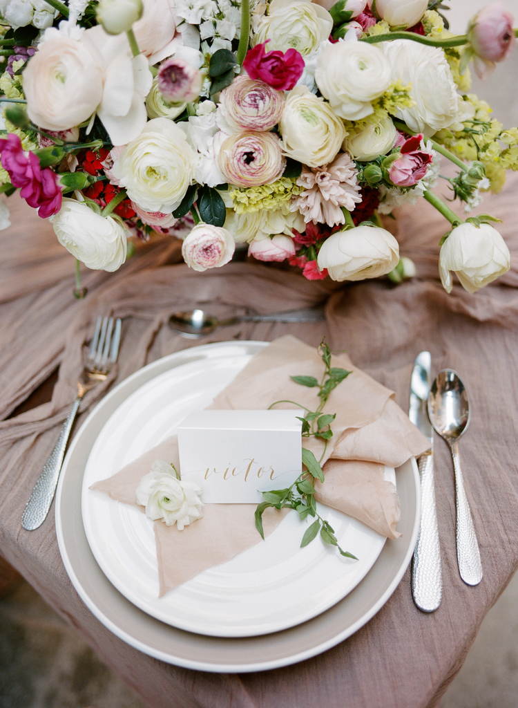 Beautiful arrangement of ranunculus, buttercups and sweetpeas on a nude table linen