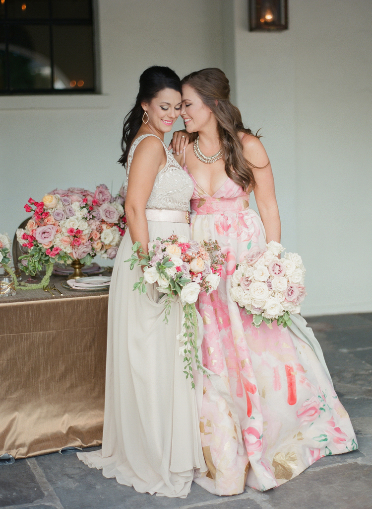 Two brides in their bridal gowns holding bouquets smiling together