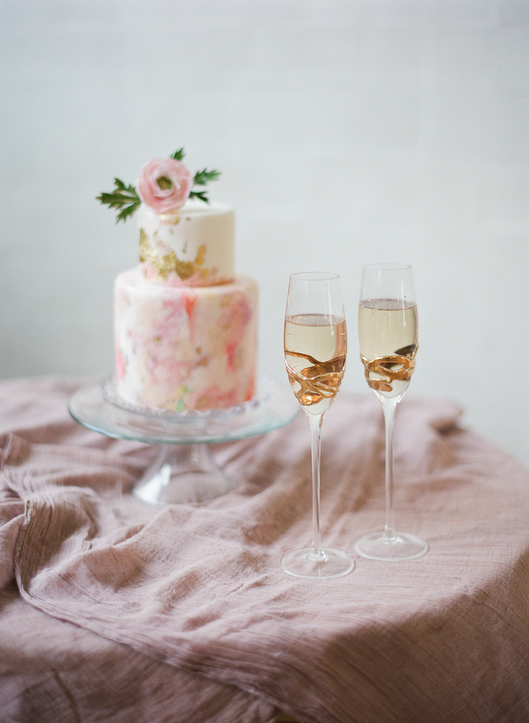 two tier Pink and gold wedding cake with a pink flower on top next to two glasses of champagne on top of a blush linen