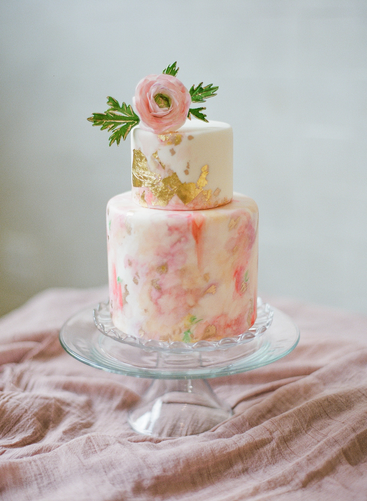 two tier pink abstract and gold leaf cake with a pink ranunculus on top
