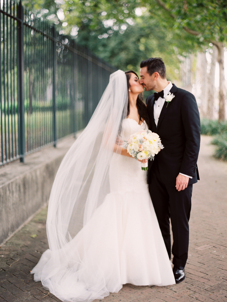 Bride and groom kissing in her wedding gown and his tux in front of an iron gate