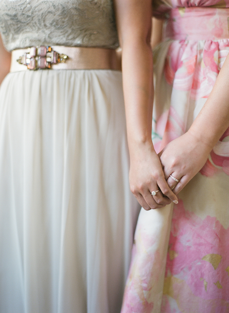Detail photo of the brides dresses with pink tones matching each other and holding hands