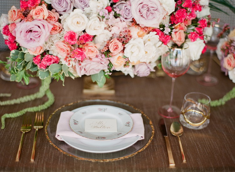 Gold flatware and gold edged plates with white escort cards in front of a lush bouquet of pink, violet and peach floral arrangement
