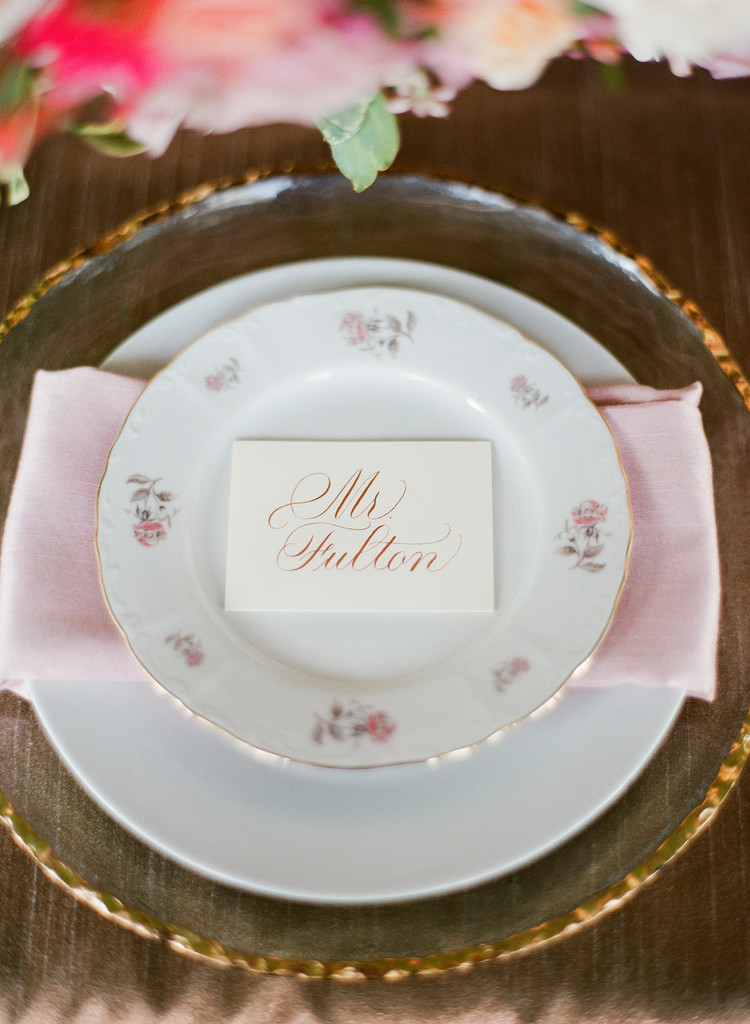 White escort card with blush lettering sitting on top of a white antique plate with pink flowers