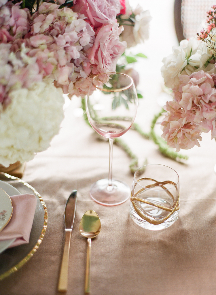 Purple and hydrangeas, pink roses next to pink and gold wine glasses