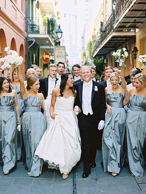 bride and groom walking with bridesmaids smiling and laughing outdoors