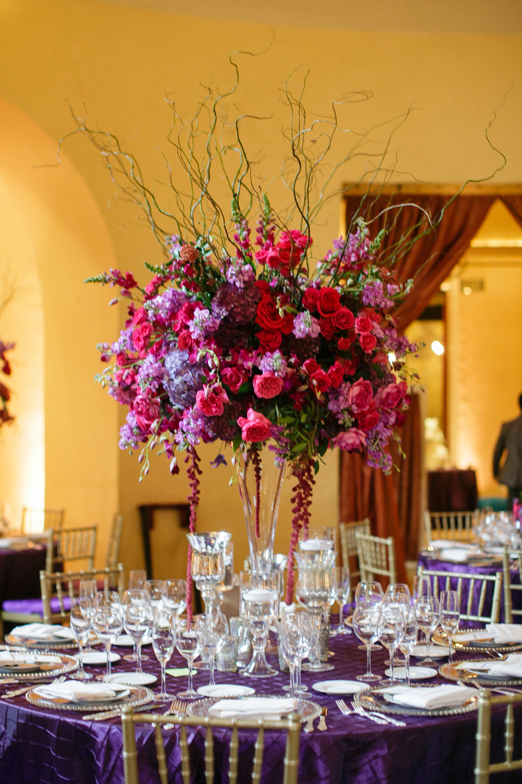 Tall Bright red and purple floral table centerpieces on top of a plum purple linen