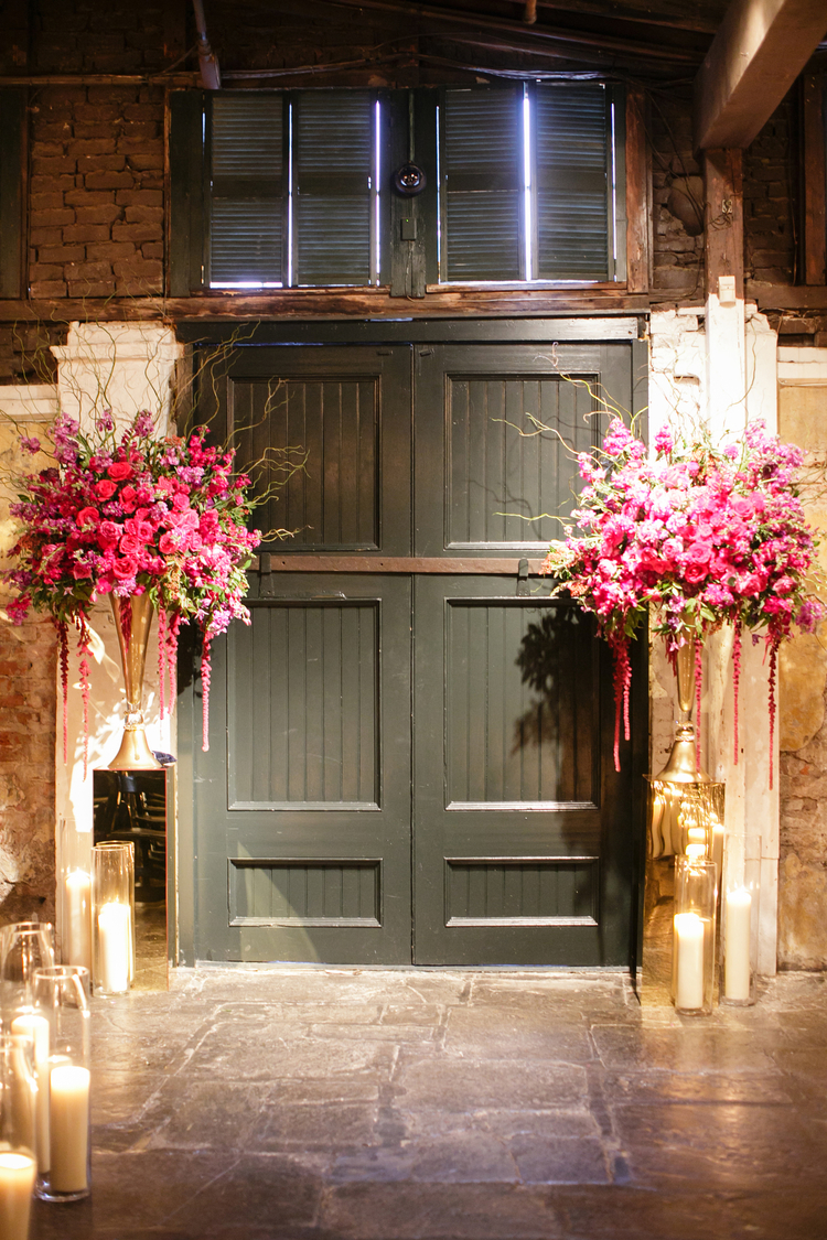 Two large pink and purple floral arrangements on either side of the entrance door to the wedding venue