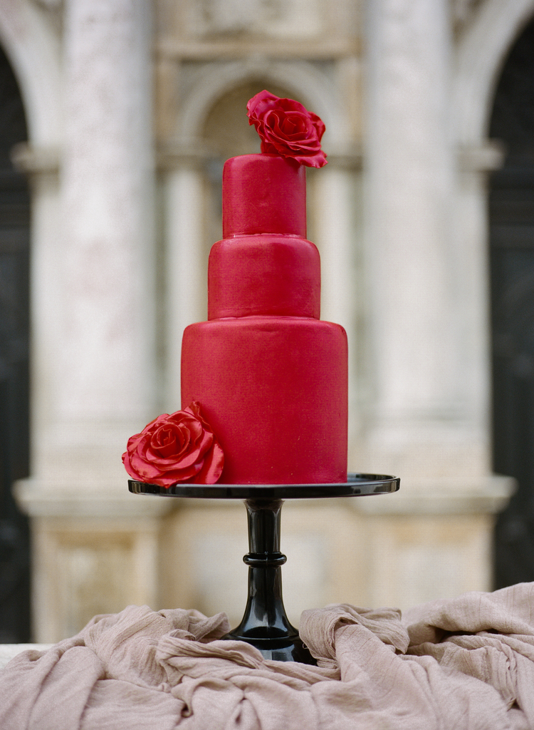 Close up of the three tiered dark red cake with two red roses delicately placed