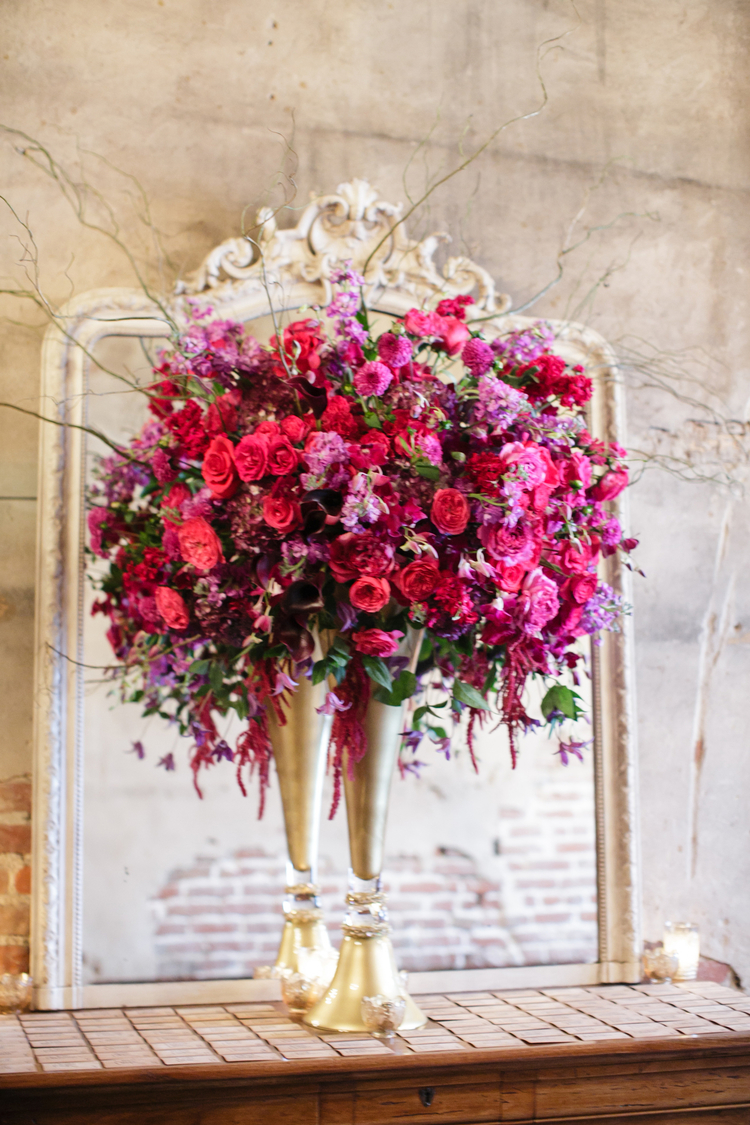 Tall, lush floral arrangement in front of a mirror with pink and red roses and purple flowers