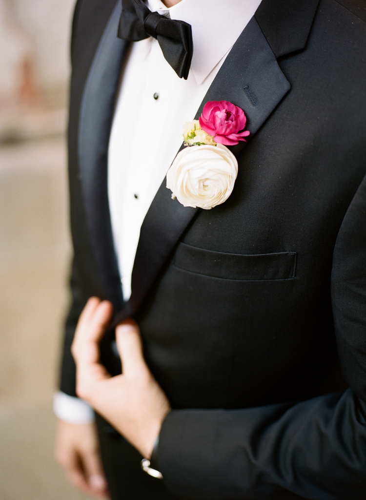 Grooms black and white tux with a white and pink buttercup flower boutonniere