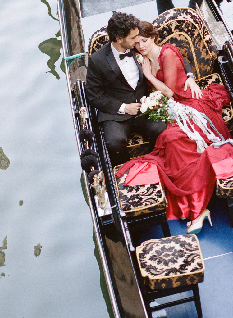 Bride laying with her groom in a gondola with black and gold detailing