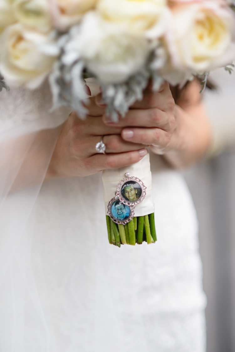 Bride holding her white floral bouquet with her grandparents pictures pinned to the stems