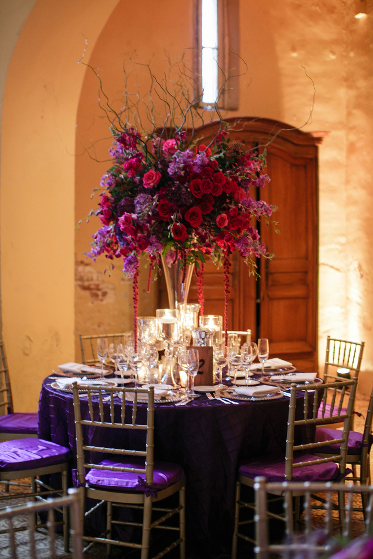 Bright red and purple floral table arrangements on top of a plum purple linen
