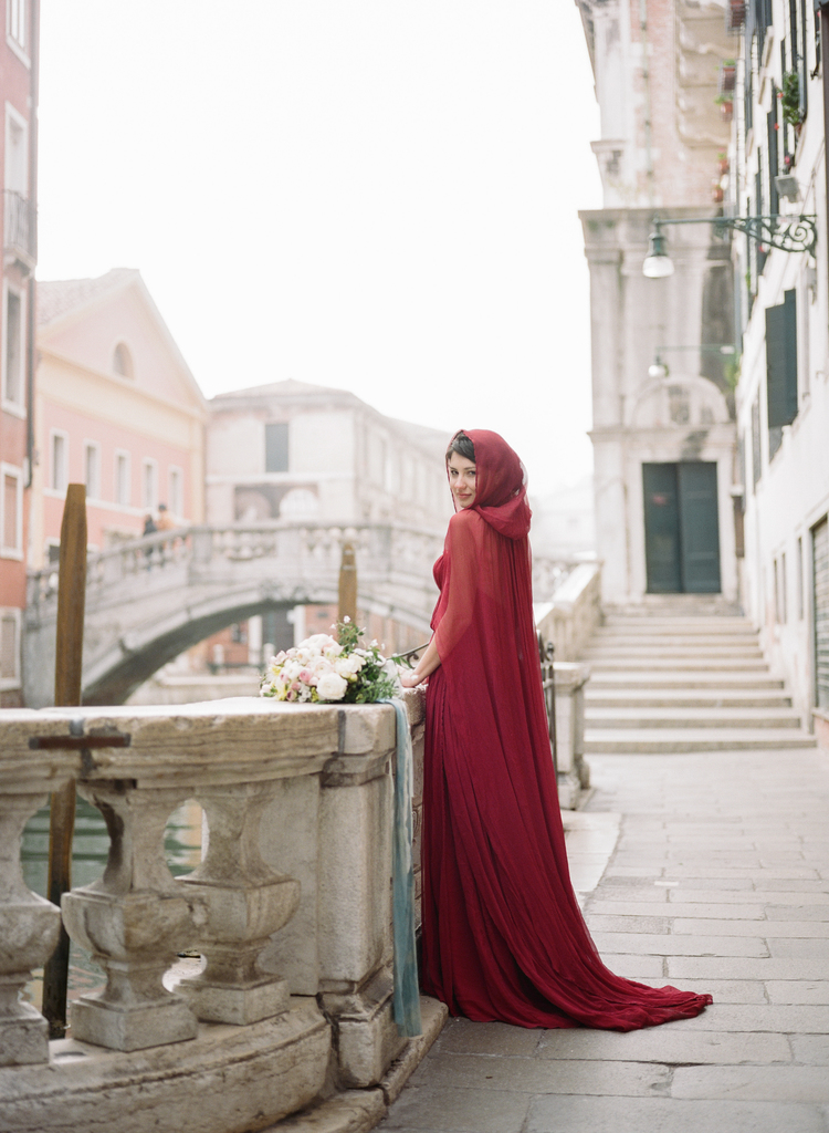 Bride in her red long dress with her hood on with white bouquet and mint sash