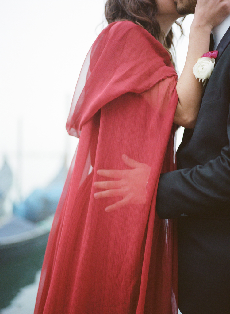 Groom holding his bride in her long sheer red caped dress