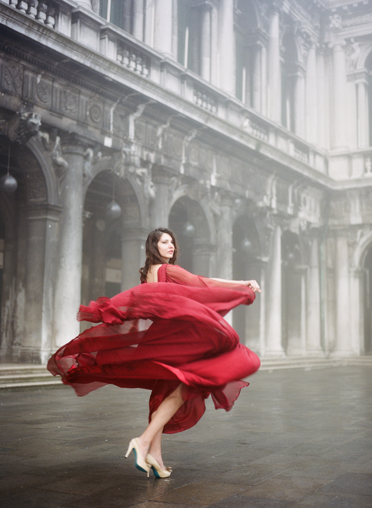 Bride twirling her in red dress and gold shoes in Piazza San Marco