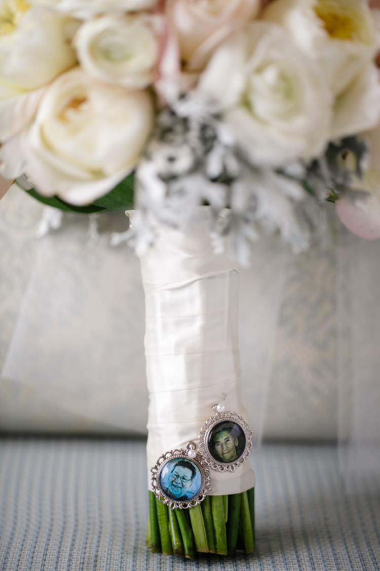 Bridal bouquet wrapped in white silk ribbons with pins of grandparents in the stems