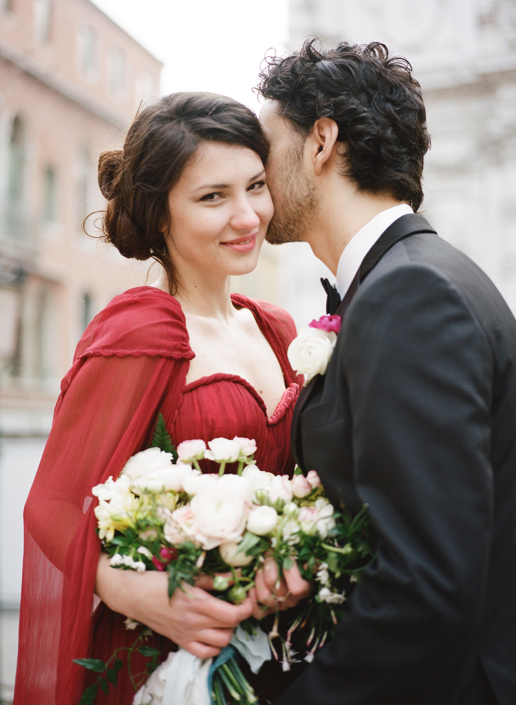 Groom kissing bride on the cheek while she holds her white floral bouquet