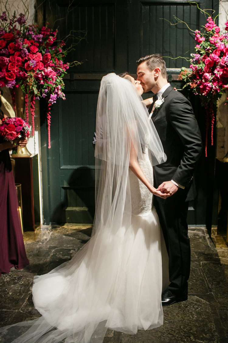 Bride and groom kiss in front of green entryway doors with two beautiful floral arrangements