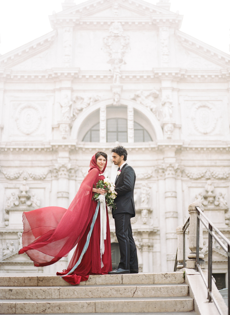 Bride in her long red dress flowing in the wind, sashes hanging from her bouquet and groom standing on the top of steps in Venice, italy