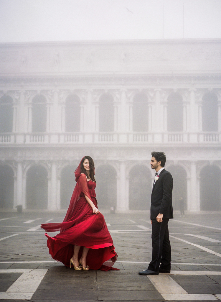 Bride twirling her red dress in the Piazza while groom gazes at her