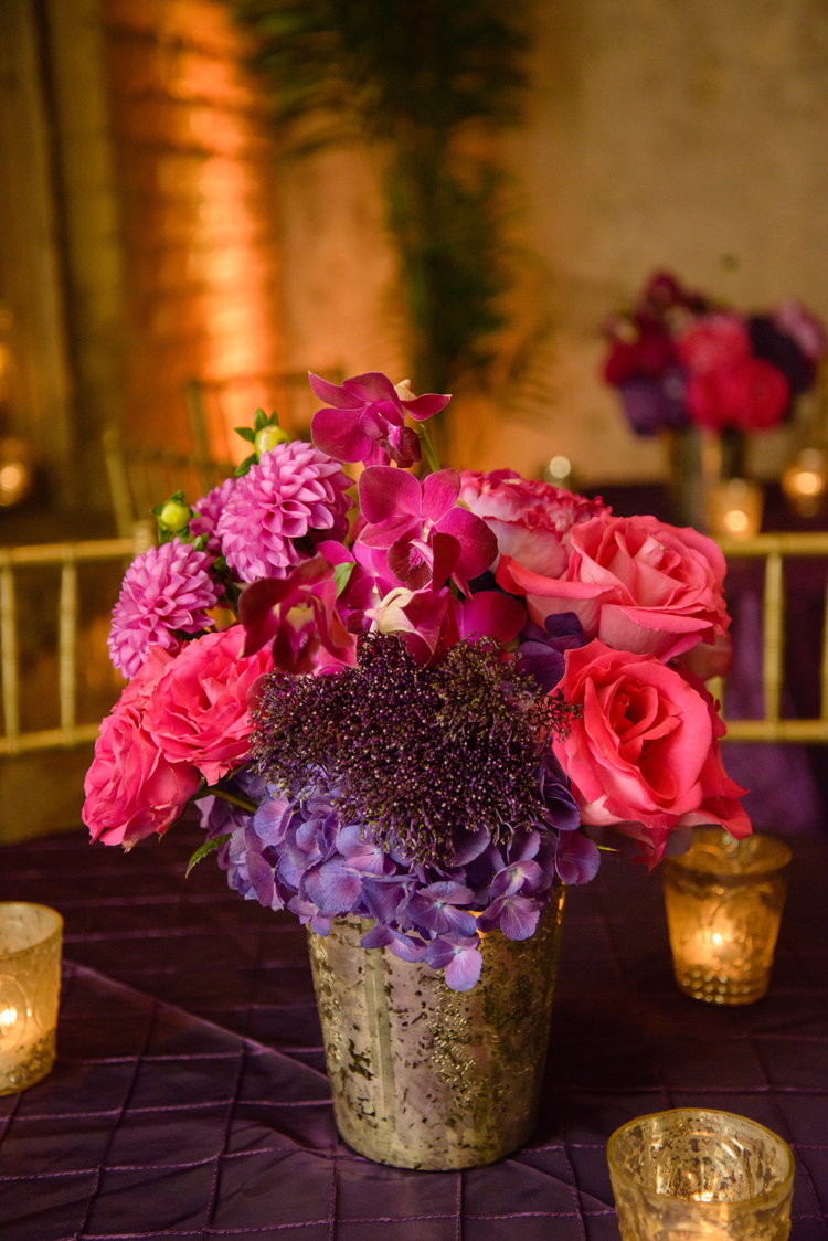 Pink roses, purple hydrangeas and pink orchids in a mercury glass vase on a purple table linen
