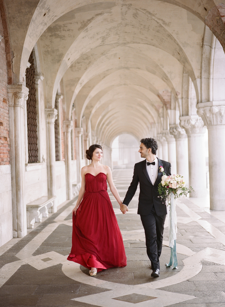 Couple walks hand in hand under a arched walkway with pillars on each side