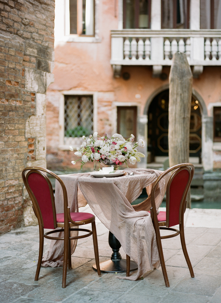 Nude table linen with gorgeous florals on top and red and mahogany chairs for a sweetheart table