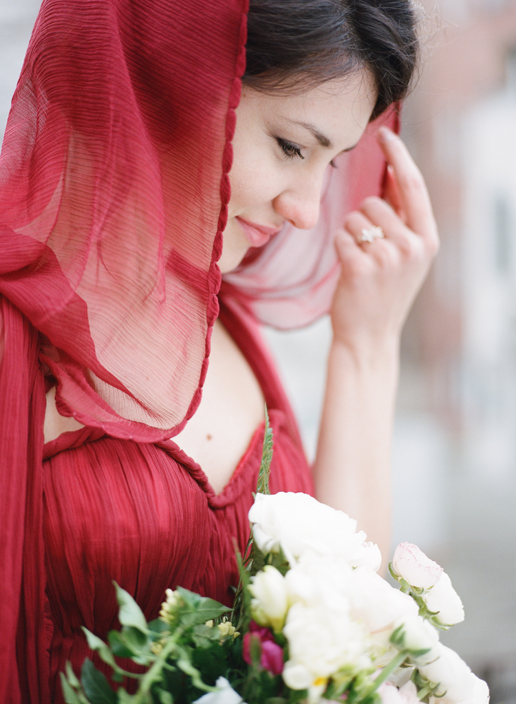 Bride holding her red hood in her red dress gazing gown at her bouquet of flowers