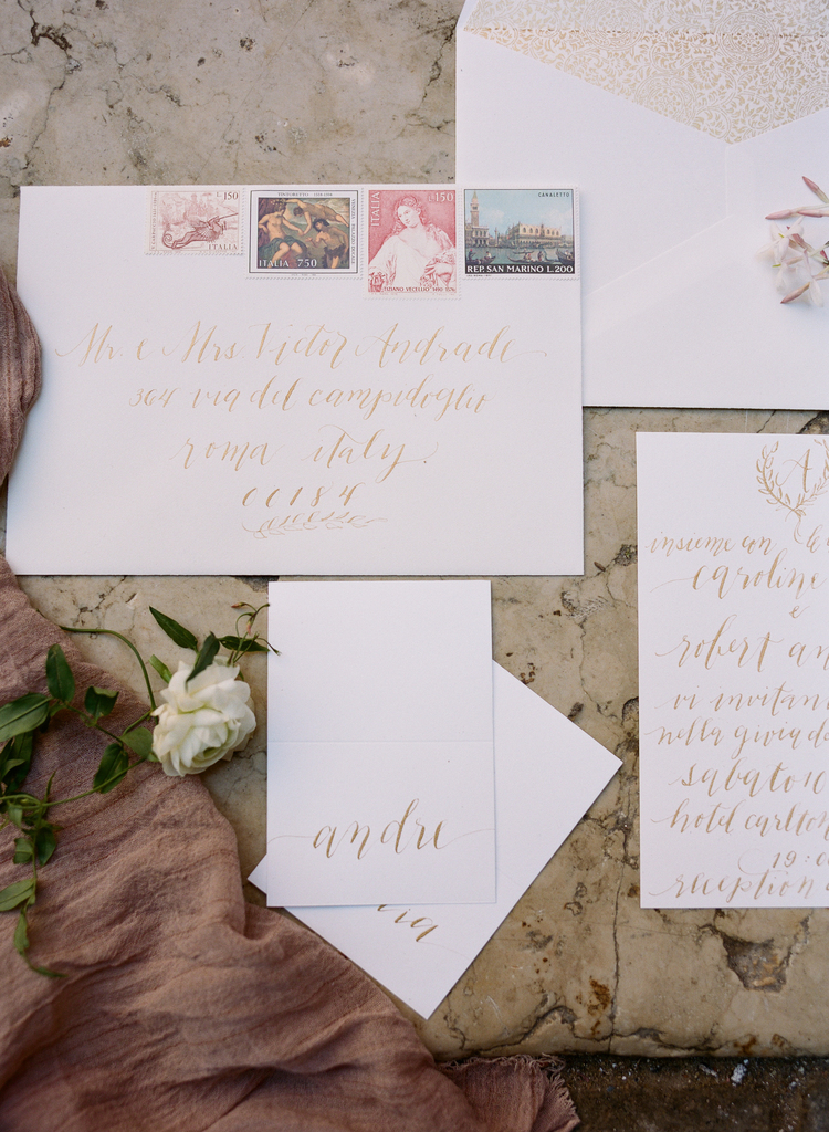 White wedding invitations with gold writing and blush stamps