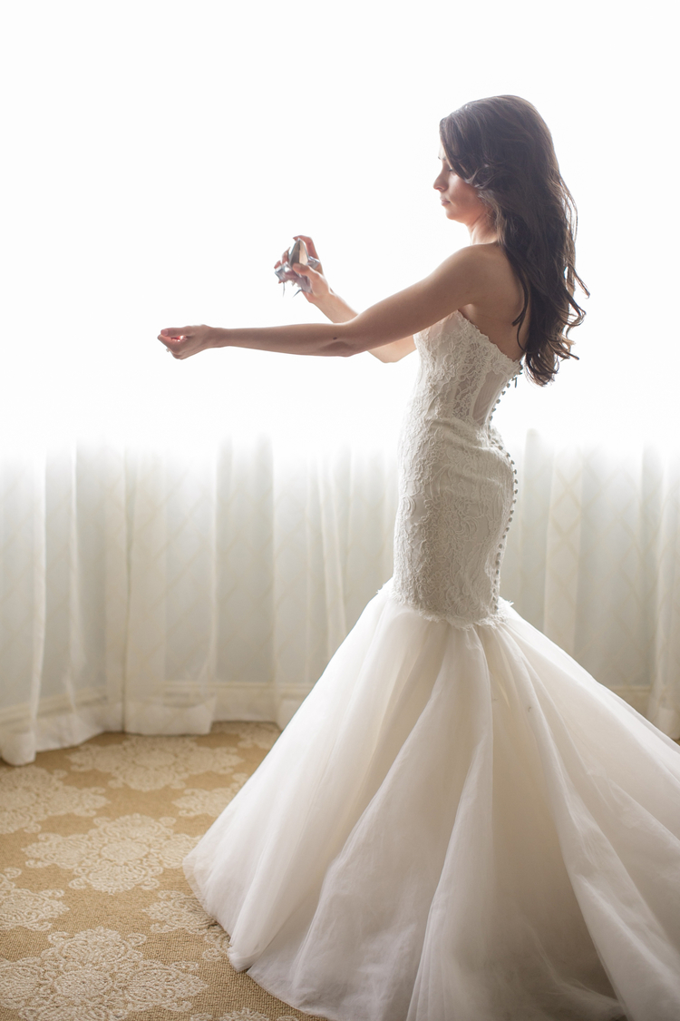 Bride putting on perfume in her white trumpet style wedding dress